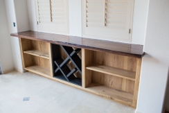 Wine storage cabinet with LED backlit bottle rack and claro walnut counter top.